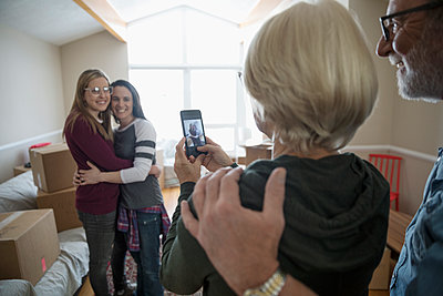 Parents with camera phone photographing hugging lesbian couple moving into new house - p1192m1560013 by Hero Images