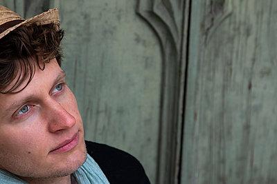 Junger Mann mit Strohhut vor grüner Holztür - p1650m2231572 von Hanna Sachau
