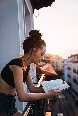Beautiful young woman on balcony above the city at sunset reading a book - p300m2042260 von Kike Arnaiz