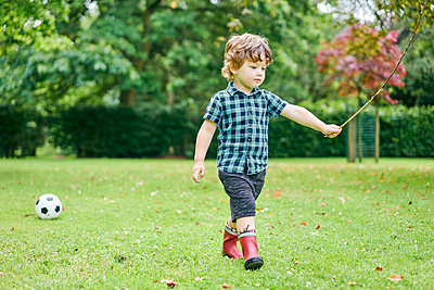 Toddler playing with stick and football in park - p429m2164641 by GS Visuals