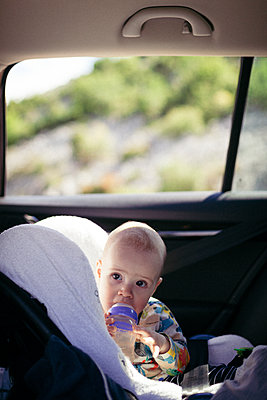 Portrait of toddler sitting in child's seat in a car  - p795m2163795 by JanJasperKlein