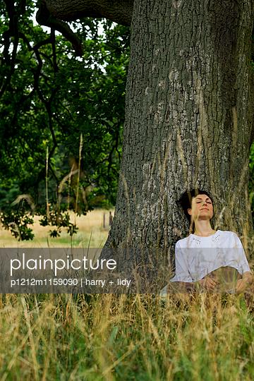 Junge Frau sitzt unter einem Baum - schläft - p1212m1159090 von harry + lidy