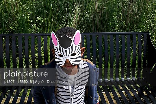 Junge als Zebra verkleidet sitzt auf einer Bank - p1307m1585018 von Agnès Deschamps