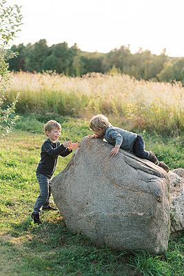 Toddler boys climbing a rock together. - p1166m2151883 by Cavan Images