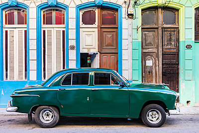 Green vintage car parked in front of house entrances, Havana, Cuba - p300m2114278 by hsimages
