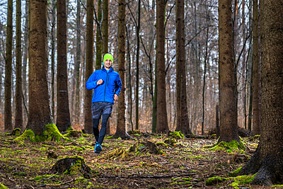 Male jogger with knit hat running through trail in forest - p300m2256628 by Stefan Schurr