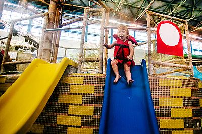 Caucasian girl riding slide at water park - p555m1306027 by Aleksander Rubtsov