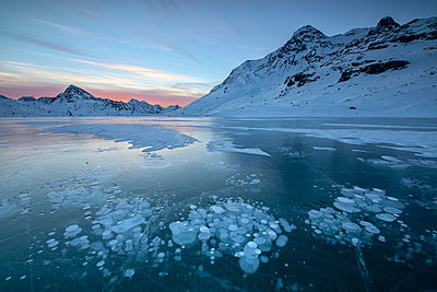 Ice bubbles frame the snowy peaks reflected in Lago Bianco, Bernina Pass, canton of Graubunden, Engadine, Switzerland, Europe - p871m1448409 by Roberto Moiola