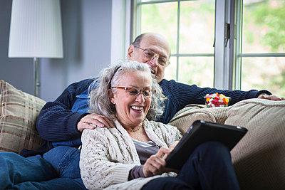 Senior couple using digital laptop on sofa at home - p924m664858f by Steve Prezant