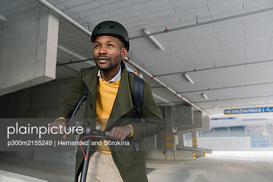 Portrait of stylish man with helmet and scooter in the city - p300m2155249 by Hernandez and Sorokina