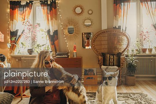 Woman dressing up dogs - p312m2237283 by Sanne Brännström