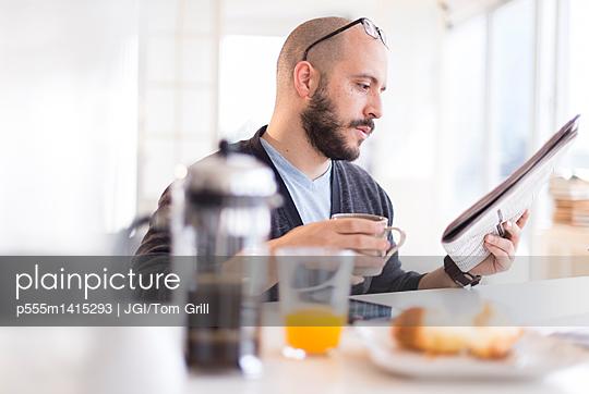 Hispanic man reading newspaper at breakfast - p555m1415293 by JGI/Tom Grill