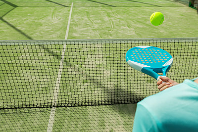 Midsection of woman hitting tennis ball with racket on court - p1166m1571070 by Cavan Social