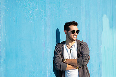 Portrait of young bearded man with sunglasses leaning against wall - p1166m2131197 by Cavan Images