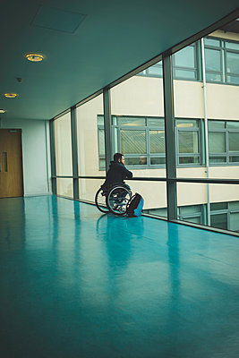 Handicapped man on wheelchair looking out from glass pane - p1315m1579182 by Wavebreak