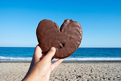 Hand holding chocolate heart on beach - p1423m2020606 by JUAN MOYANO