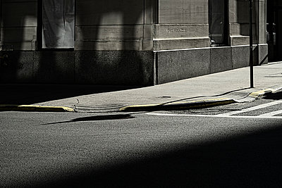 Shadowed road, pavement and building corner - p301m960786f by Michael Mann