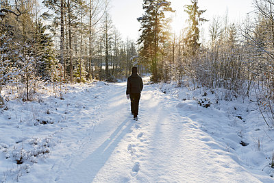 Mature woman walking on snowy road - p352m2120025 by Åke Nyqvist