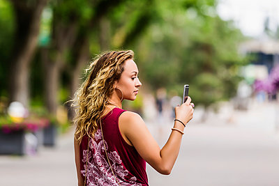 A beautiful young woman walking down a street near a university campus messaging using video on her smart phone; Edmonton, Alberta, Canada - p442m2004185 by LJM Photo