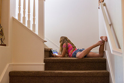 Caucasian girl using digital tablet on stairs - p555m1410689 by Marc Romanelli