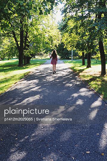 Teenager im lila Outfit geht durch einen Park - p1412m2029065 von Svetlana Shemeleva