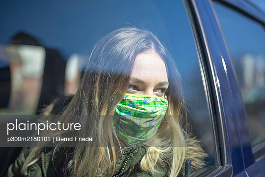 Portrait of young woman wearing mask in car - p300m2180101 by Bernd Friedel