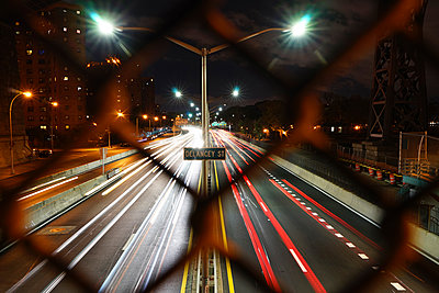Light trails on city street seen through fence - p1166m1185927 by Cavan Images