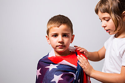 6-year-old girl wrapping the U.S. flag around her 4-year-old brother - p1166m2193945 by Cavan Images
