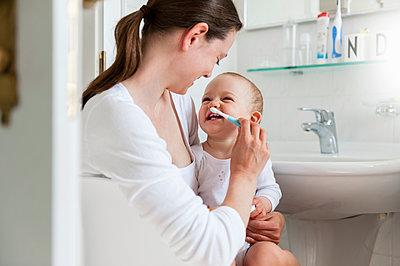 Mother brushing baby's teeth in bathroom - p300m1587821 by Daniel Ingold
