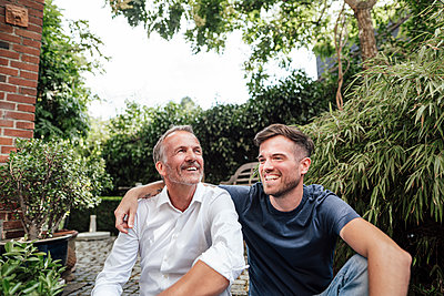 Father and son relaxing while sitting in backyard - p300m2275074 by Gustafsson