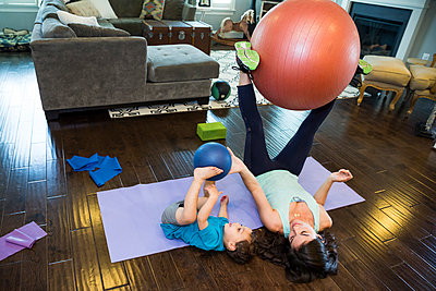 Mother and son playing with exercise ball - p555m1408365 by Shestock