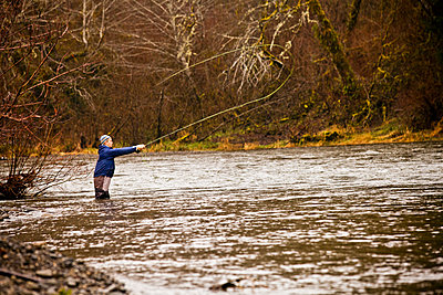 Man fly fishing in rural river - p555m1419805 by Adam Hester