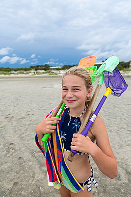 Caucasian girl on beach carrying net and shovels - p555m1522727 by Marc Romanelli