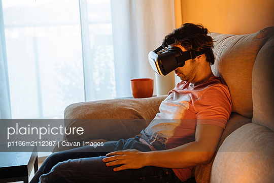 Man using virtual reality while sitting on sofa at home - p1166m2112387 by Cavan Images