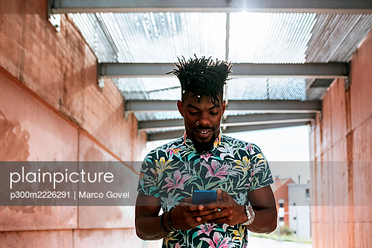 Close-up of African man using smart phone while standing amidst walls - p300m2226291 by Marco Govel
