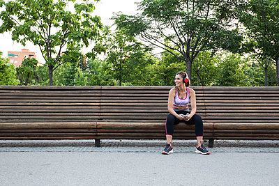 Fit girl with phone looking away on bench - p1166m2130085 by Cavan Images