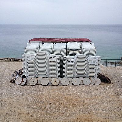Stacked sunloungers on the waterfront - p1401m2260653 by Jens Goldbeck