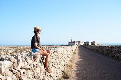 Spain, Menorca, single traveller sitting on natural stone wall looking at view - p300m1499365 by Ivan Gener Garcia