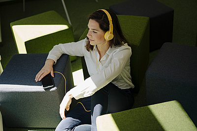 Woman with headphones listening music while sitting on floor in office - p300m2221034 by Joseffson