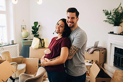 Smiling man embracing pregnant woman while standing against boxes in living room - p426m1542773 by Maskot
