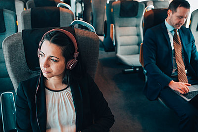 Businesswoman using headphones while traveling with businessman in train - p426m1580132 by Maskot