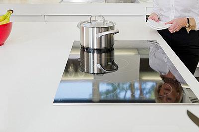 Frau steht in der Küche mit einem Kochtopf auf dem Herd - p473m670328f by STOCK4B RF