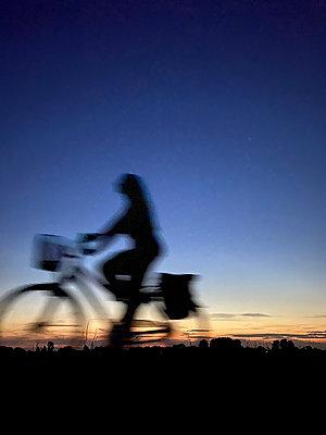 Frau auf Fahrrad in der Abendsonne, Bewegungsunschärfe - p958m2290813 von KL23