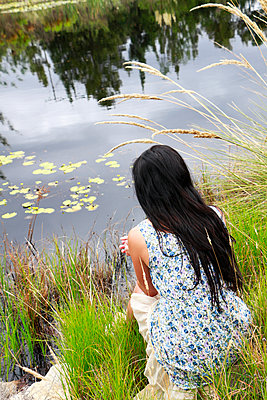 Woman sitting by a pond - p967m892215 by Wessel Wessels