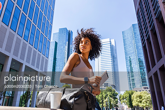 Germany, Frankfurt, portrait of young woman with travelling bag, tablet and coffee to go in the city - p300m2030333 by Tom Chance