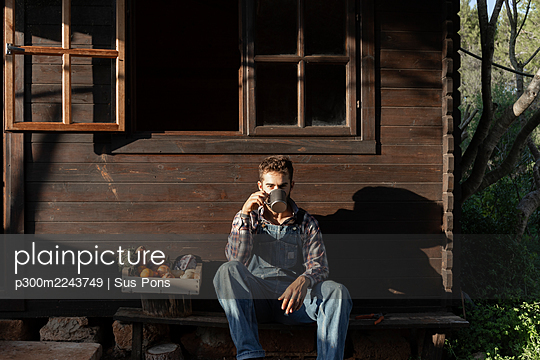 Male farmer with vegetable crate having coffee against wooden house on sunny day - p300m2243749 by Sus Pons