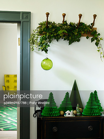 Garland of ivy on coat hook with paper Christmas trees on sideboard - p349m2167788 by Polly Wreford