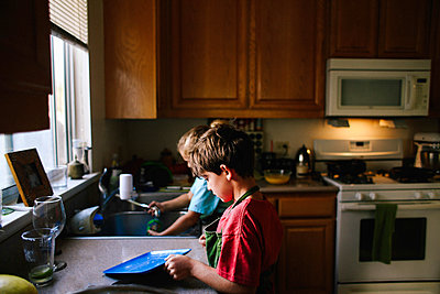 Siblings cleaning utensils in kitchen - p1166m1204399 by Cavan Images