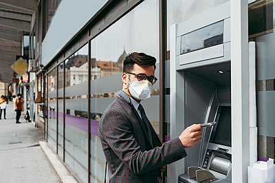 Business man with protective face mask using street ATM machine. - p1166m2179393 by Cavan Images