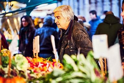 Mann betrachtet Gemüse auf dem Wochenmarkt - p1312m2082200 von Axel Killian